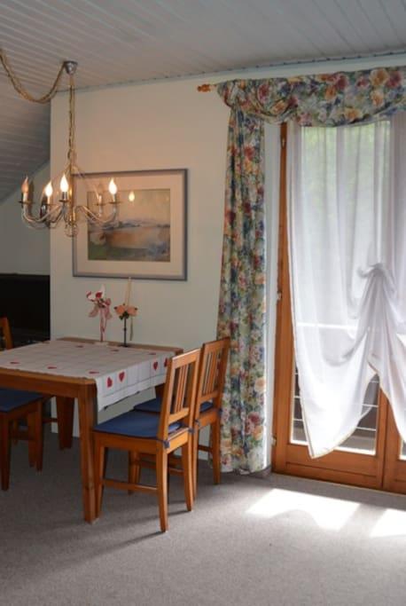 Essplatz im Wohnzimmer mit Zugang zum Balkon