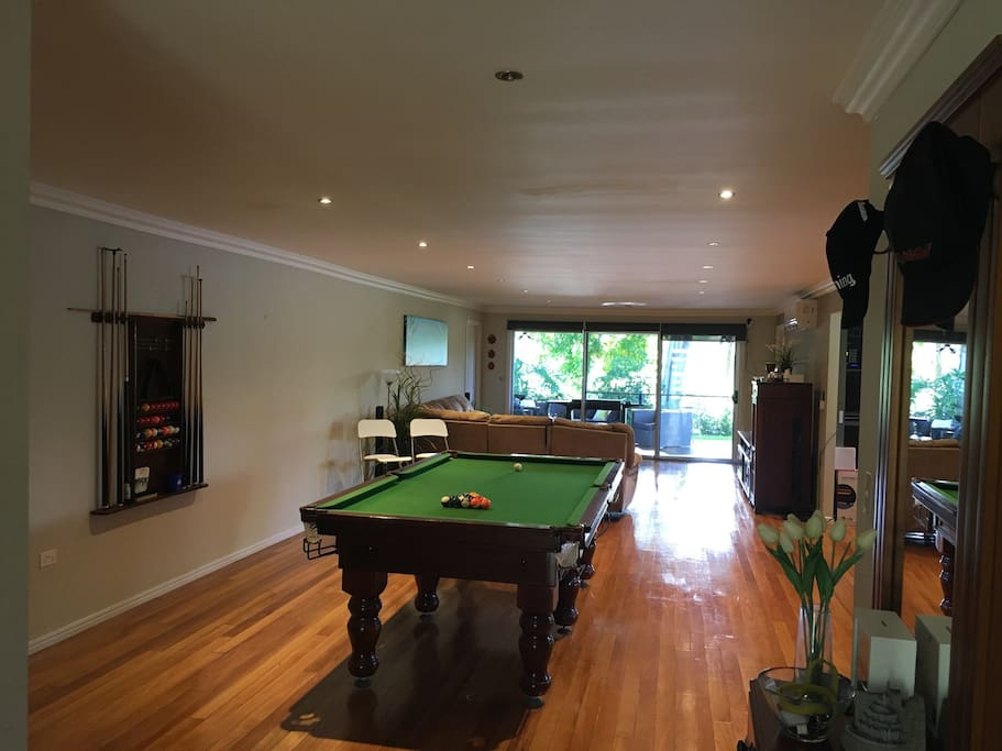View from the main entrance - pool table, lounge area and full length doors out to back deck, leafy backyard and serene lake views.