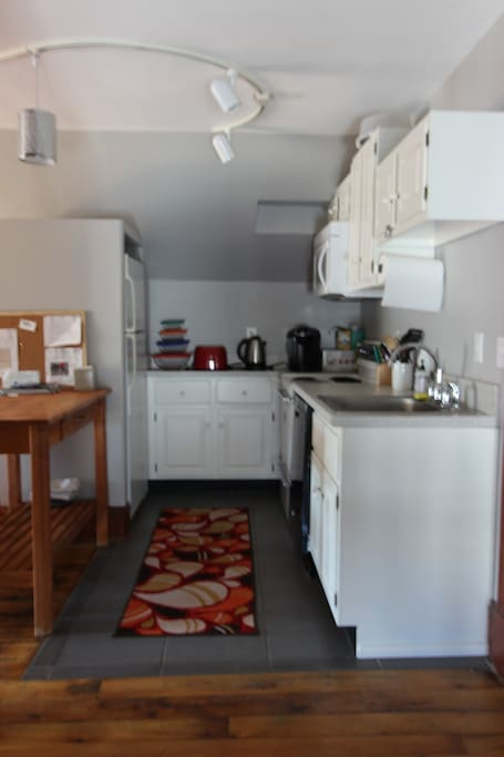 Kitchen with breakfast bar, full refrigerator/freezer,  stove, microwave, and dishwasher. Toaster, hot water boiler, pod style coffee maker & coffee pods, pots, pans, dishes, utensils, and more.