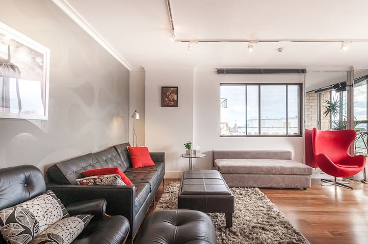 The industrial living area is spacious, with plenty of seating for six guests to enjoy time together or watch a movie.