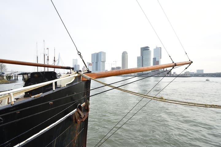 unique historical yacht from 1915 in Rotterdam, the Meuse overlooking