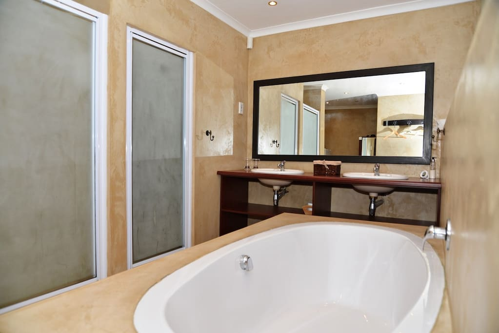 Full bathroom with oval bath, shower and double vanities