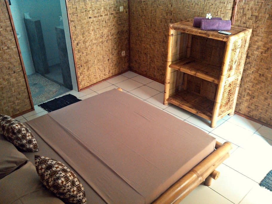 Studio room in Gili Trawangan: Mama J's Cinammon Studio / BEDROOM with BATHROOM AREA: furnished with bamboo bed, open cupboard and bedside table.