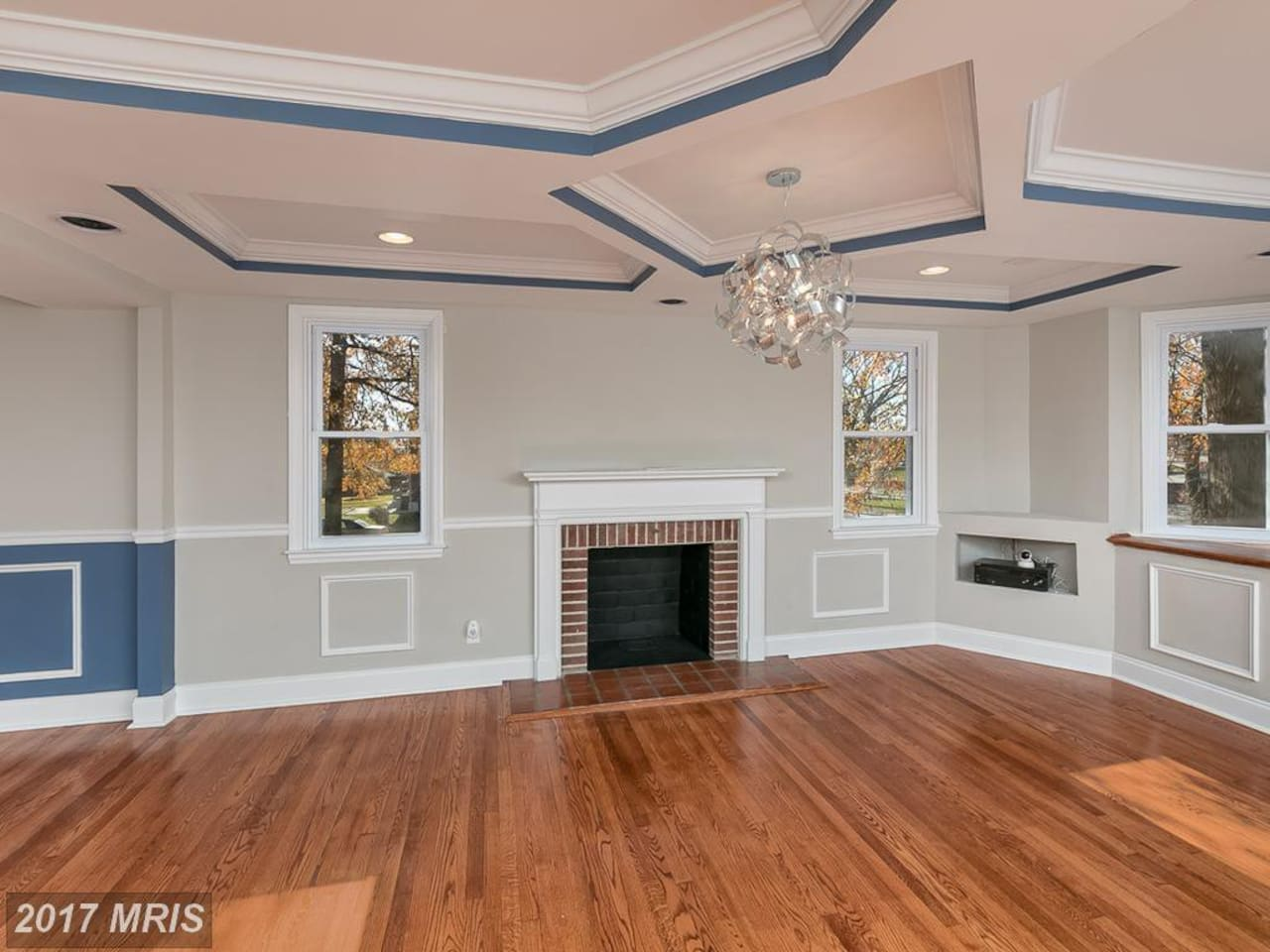 The living room has a fireplace and bay windows