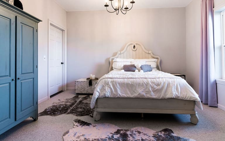"""The bedroom has a swanky/romantic feel to it. Dimmable lighting, remote controlled LED candles and moonlight are your lighting options. The blue wardrobe is the only """"closet"""" in the apartment, and there's a luggage rack as well."""