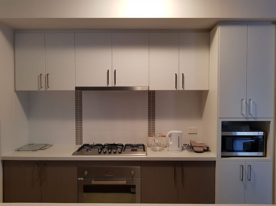 Fully equipped kitchen with gas cooktop, electric oven, fridge, kettle, toaster, dishwasher and cookware.