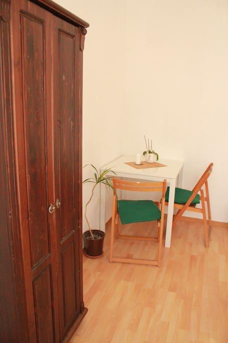 Schrank, Tisch und Stühle.