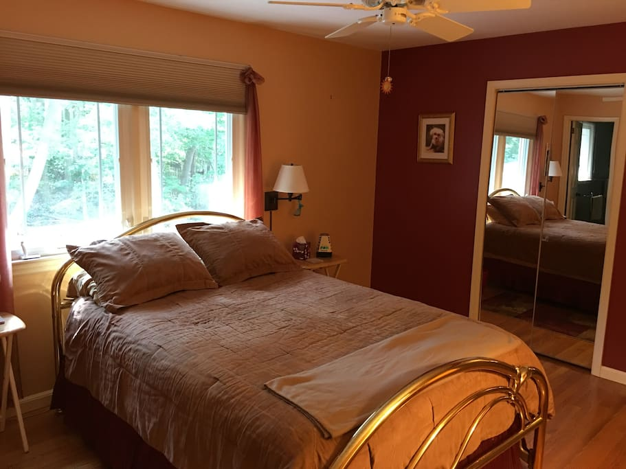 Pillowtop queen bed in clean, comfortable room with hardwood floors.