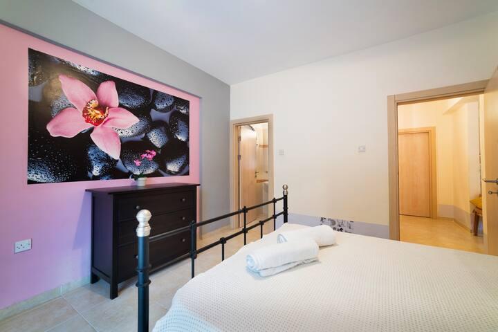 Родительская спальня с большой двуспальной кроватью и собственным туалетом и выходом на террасу.