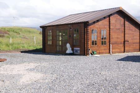 Log cabin beside historic Broch