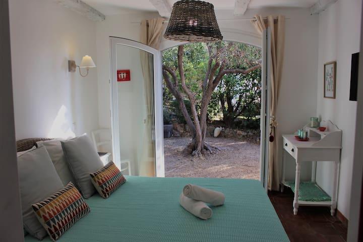 la chambre ouverte sur le petit jardin privé à l'ombre de l'olivier