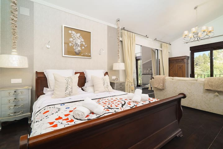 Master suite with super king bed and Juliet balcony with views of the mountains, swimming pool and  gardens.