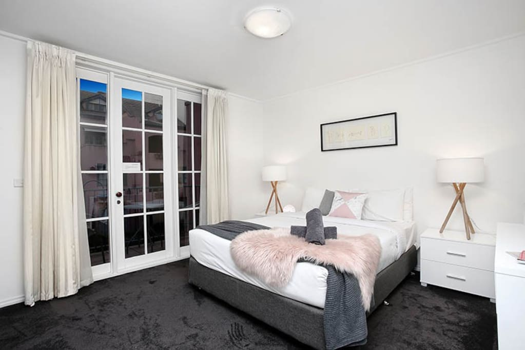 Spacious queen bedroom with lots of hanging space, mirrors on the wardrobe doors, and overlooking a beautiful Tuscan courtyard; in this 1-bedroom StayCentral St Kilda Serviced Apartment