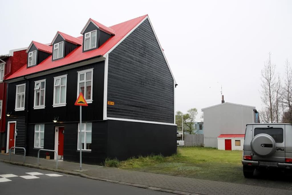 The house is newly painted black with a red roof