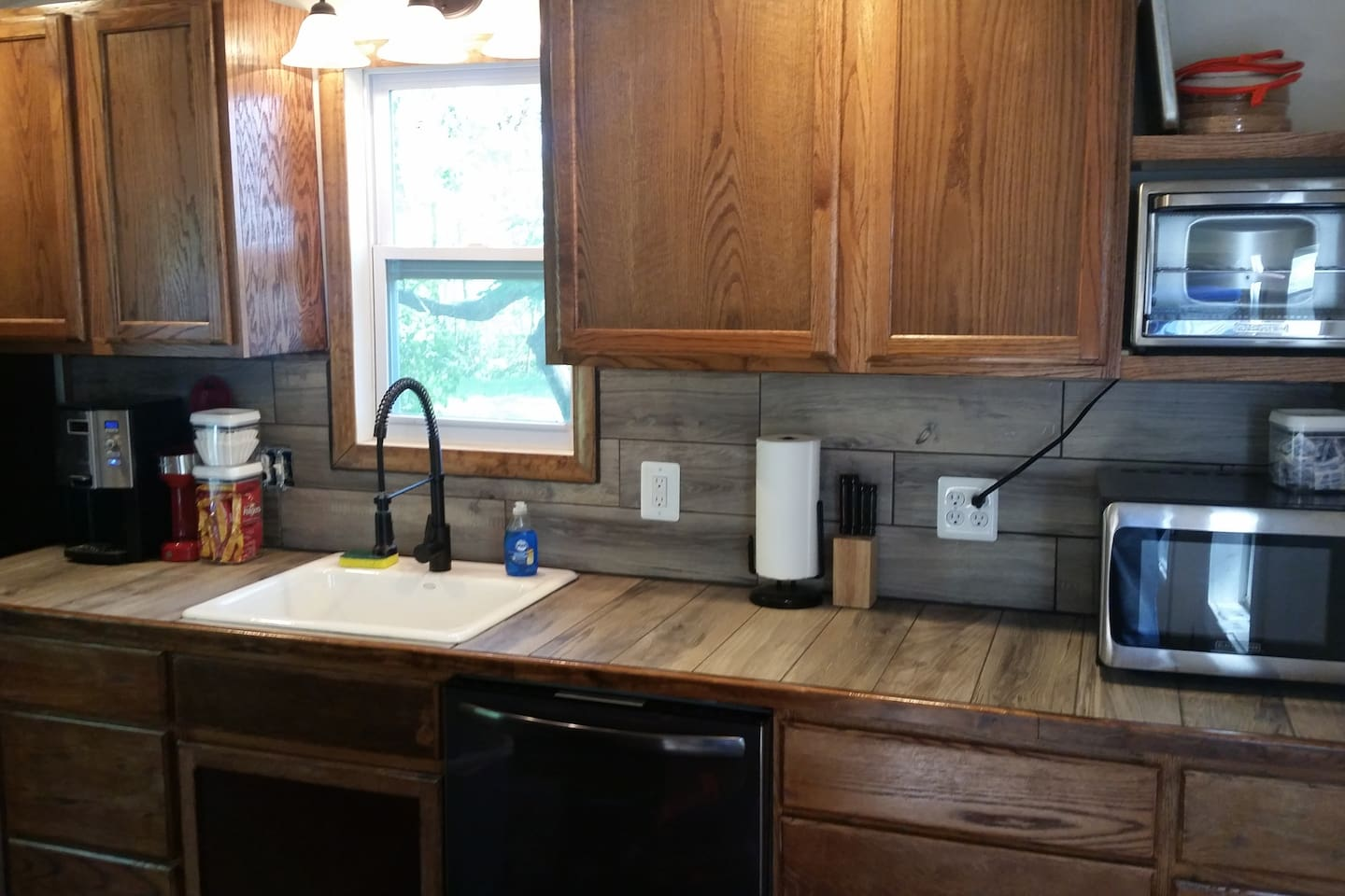 A complete kitchen that includes a drip coffee pot, a single serve maker, microwave, toaster oven, and  is fully equipped with side by side refrigerator freezer, dishwasher and gas range.