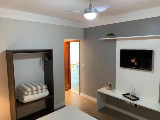 Televisão aberta e armário arejado com cabides e espaço para malas.