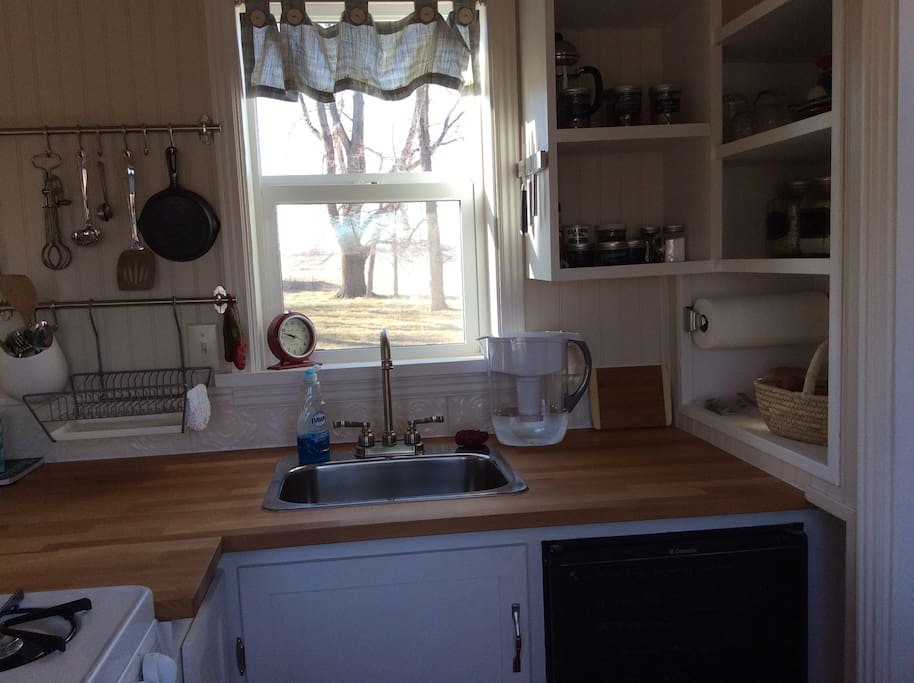 The kitchen holds a small refrigerator stocked with fresh farm food, an apartment stove, and cupboards filled with basic ingredients.