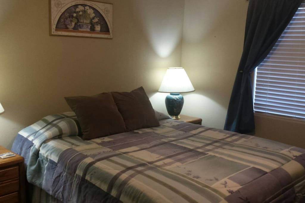 Bedroom with queen bed and room darkening curtains