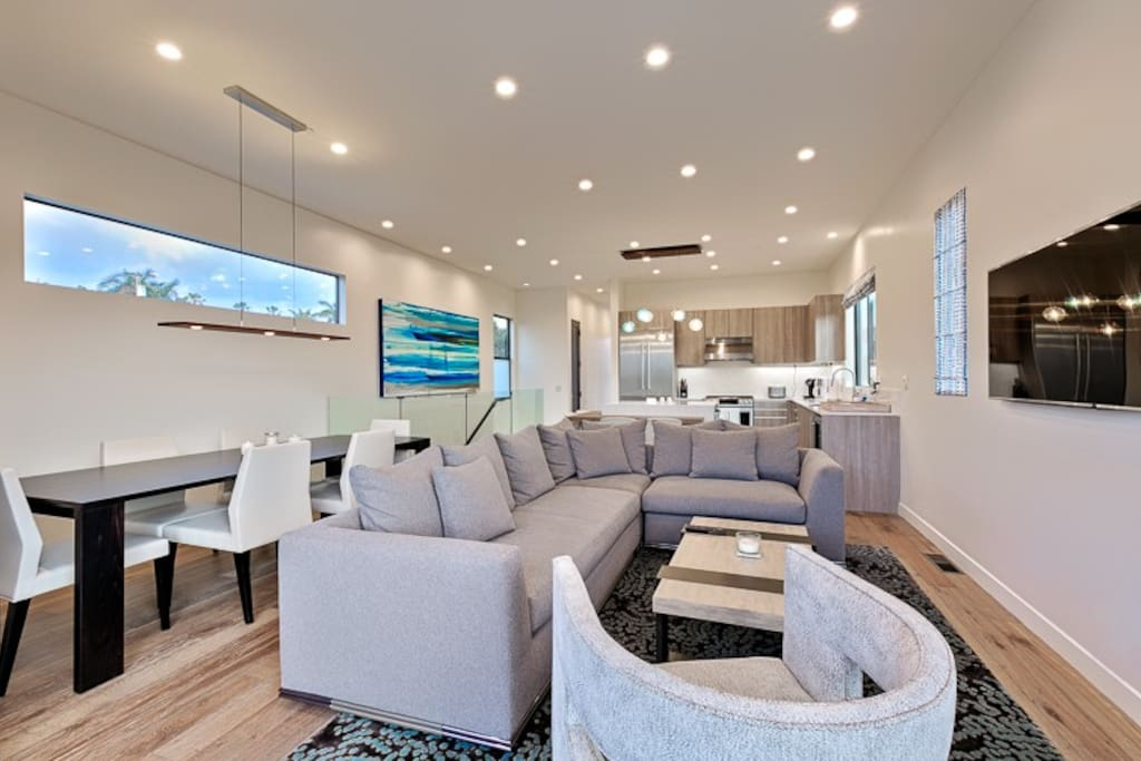 """Inviting Great Room with 48"""" TV, a dining are and a peek of the kitchen in the background."""
