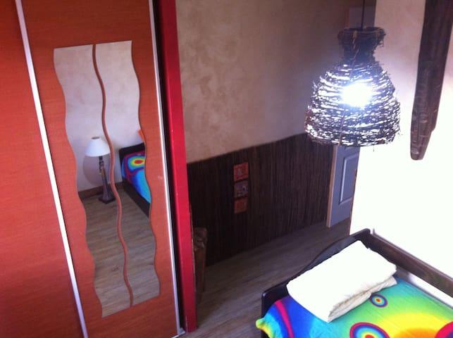 Chambre déco Afrique avec un lit gigogne un bureau et une armoire