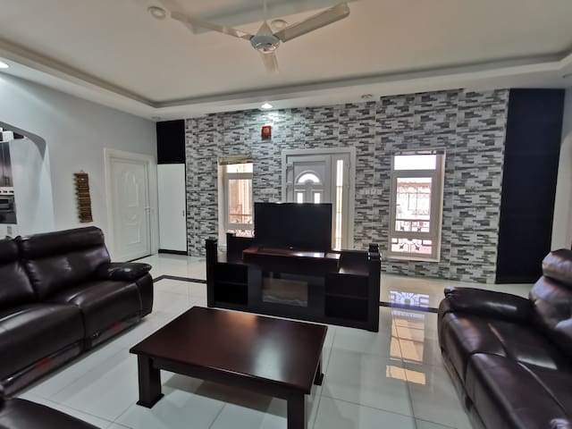 The living room has artificial leather and declining seats enough for 7 to 8 people. It has a satellite and smart TV with unlimited and strong Wi-F.