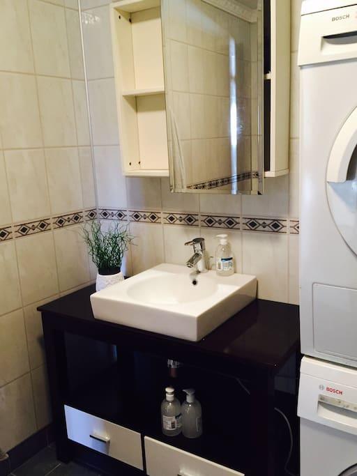 Baderom med vask og tørketrommel . Dusj  og håndvask . Hånduker er inkl i leien