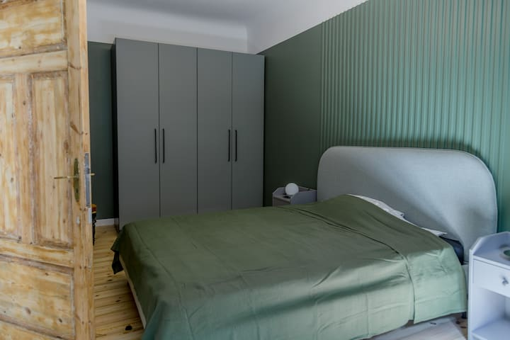 The bedroom has a queen-sized (160 cm wide) bed and a large closet with hangers inside.