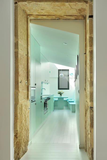 A l'entrée en pierres dorées de la cuisine avec espace repas au fond