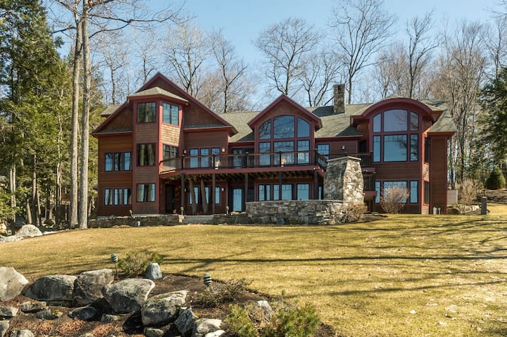 Sprawling lakefront estate with six bedrooms, outdoor kitchen, private beach, and boat docks