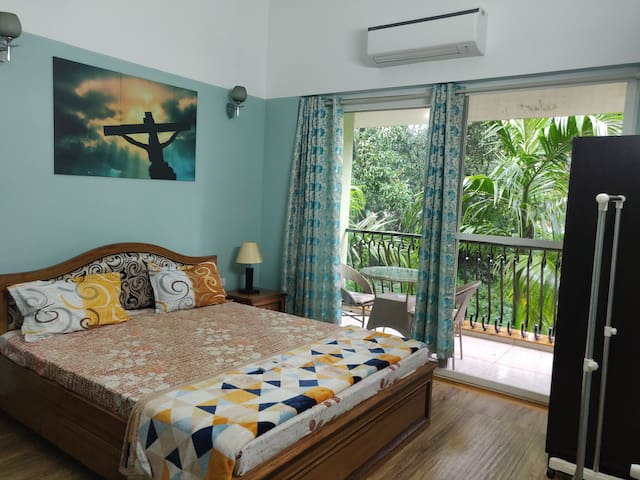 1st Floor Air conditioned Bedroom with balcony overlooking the garden with outdoor sitting.