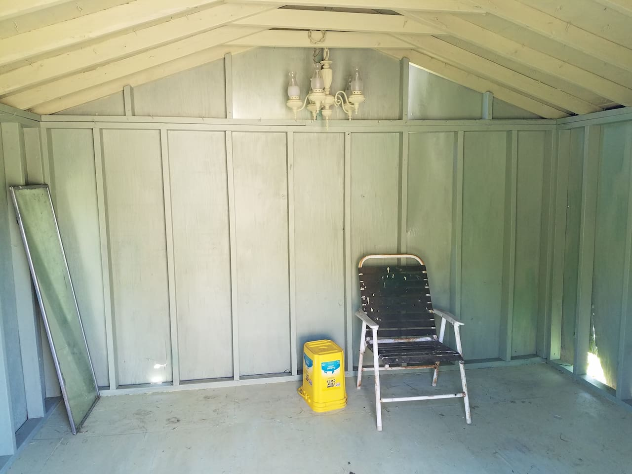 This is the inside of your shed.   It has no electricity or toilet.  There is a mirror, chair, and bucket.  The chandalier was in the shed when I purchased it, so I painted it to match.  I call it... art.  =)
