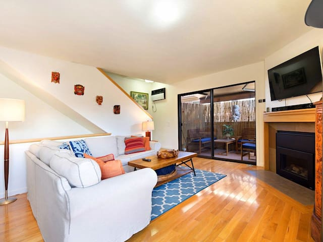 Living room area right off the outside patio has a flat screen TV  and comfortable cluster seating.