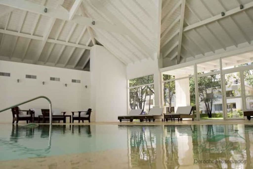 Indoor pool with steam room and sauna amenities.