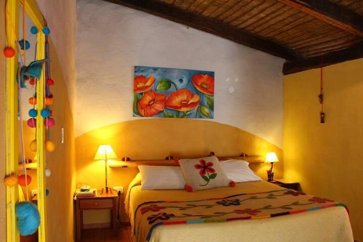 Cama extra large de la Suite Géode con adornos étnicos y artesanales, pinturas a la cal ecológicas
