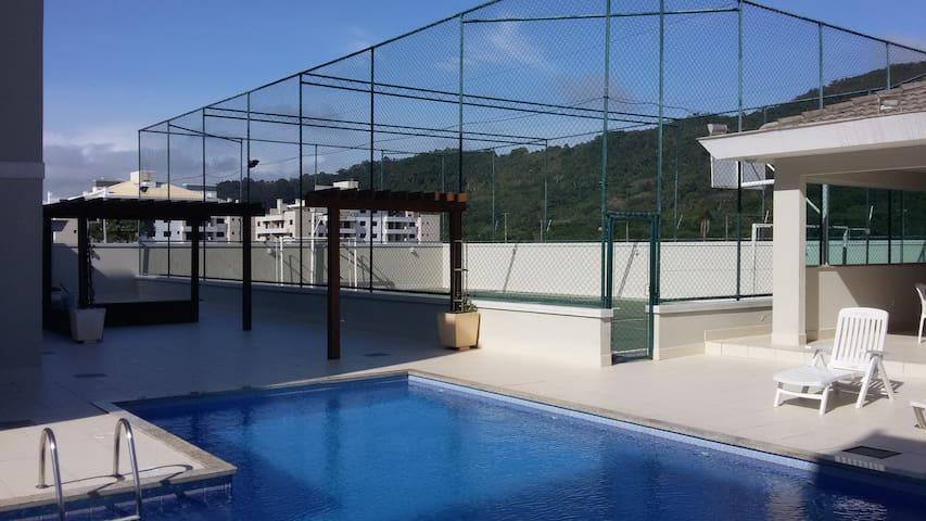 Vista da piscina e quadra de esporte multiuso
