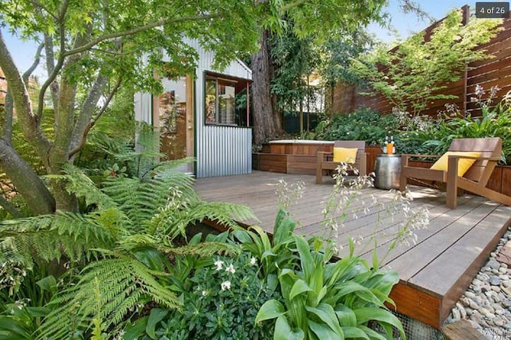 Studio with redwood tree, hot tub and deck, under Japanese Maple tree. This photo shows the old deck configuration. There is a couch, chair, and table now.