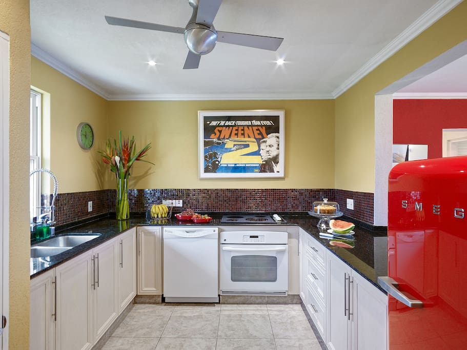 The Kitchen is modern and has all the amenities you will need for your holiday. The black granite counter tops and the colourful textured mosaic backsplash combine with the red Smeg refrigerator.