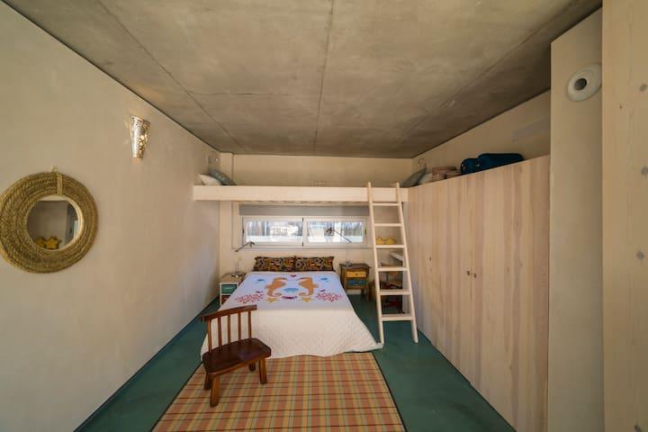 Uno de los dos dormitorios familiares gemelos  en planta baja, cama queen, litera doble, armarios, gran ventana rasgada sobre la cama, zona de trabajo tras el armario, acceso directo a la piscina y al precioso patio central.