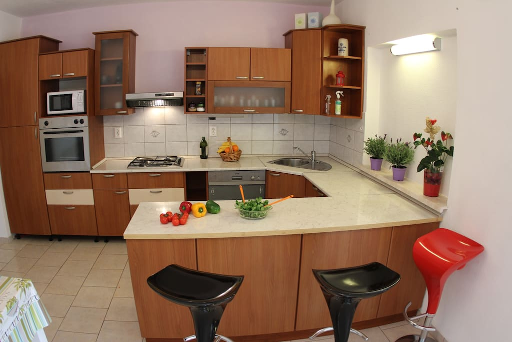 The luxurious kitchen equipped with gas burners, a refrigerator that includes a deep freezer, an oven and a dishwasher.