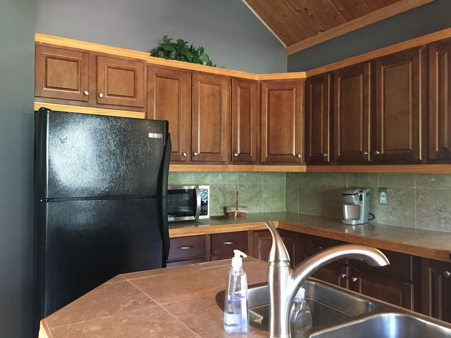 Kitchen with new microwave, full size refrigerator and coffee machine. Coffee, dinnerware, cutlery, glasses and mugs provided. The home has high ceilings making the space feel larger. It's clean and uncluttered!