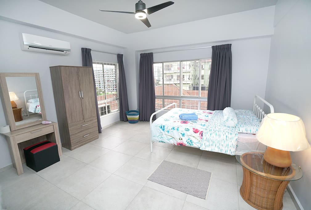 Master bed room with queen size bed. A wardrobe with hangers inside, dressing table and a hair dryer. The room is with attached bathroom with heater shower. There are also multiple socket in the room. 90% sun block curtains.
