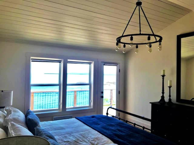 Primary bedroom on main level with amazing view, and deck access. Hear the waves at night.