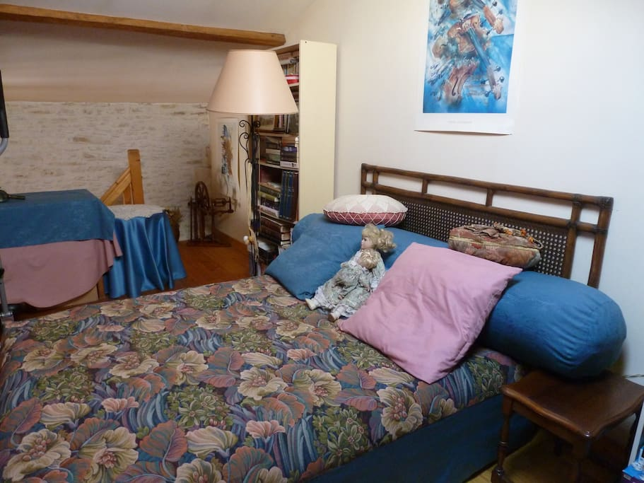 La chambre se situe en mezzanine, au dessus d'un salon séparé du reste de la maison. Lit 2 places, étagères à disposition, bureau et portant.