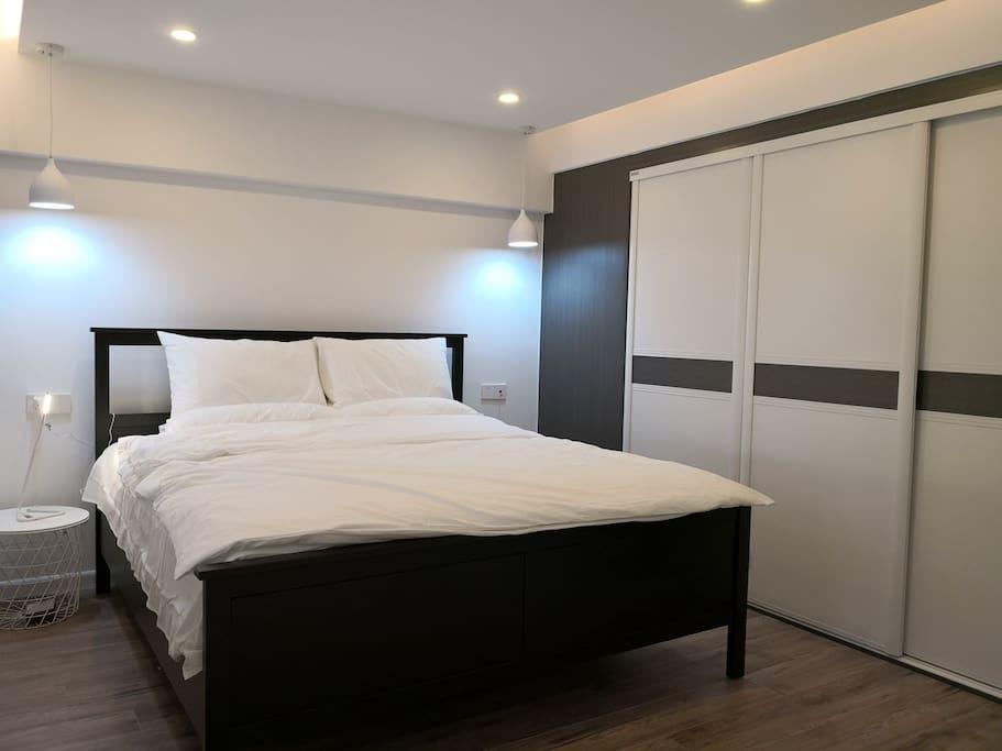 抬高式卧室,旁边是衣柜,并配有足量的衣架。