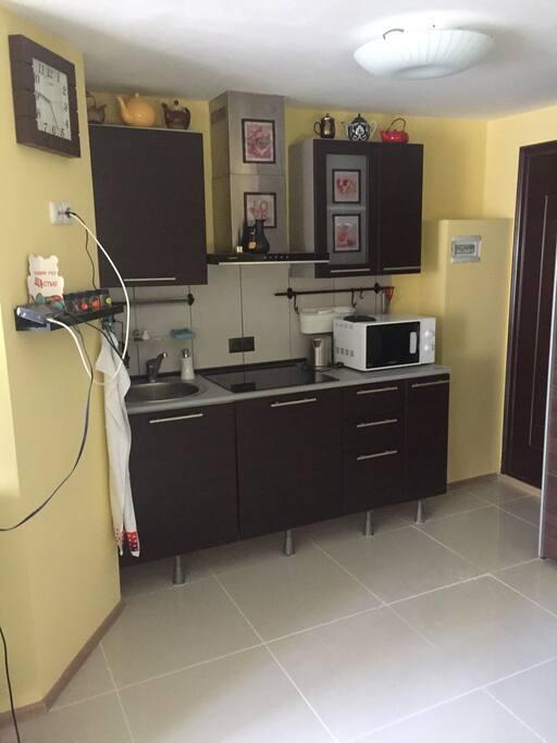 Кухня с керамической плитой и микроволновой печью.