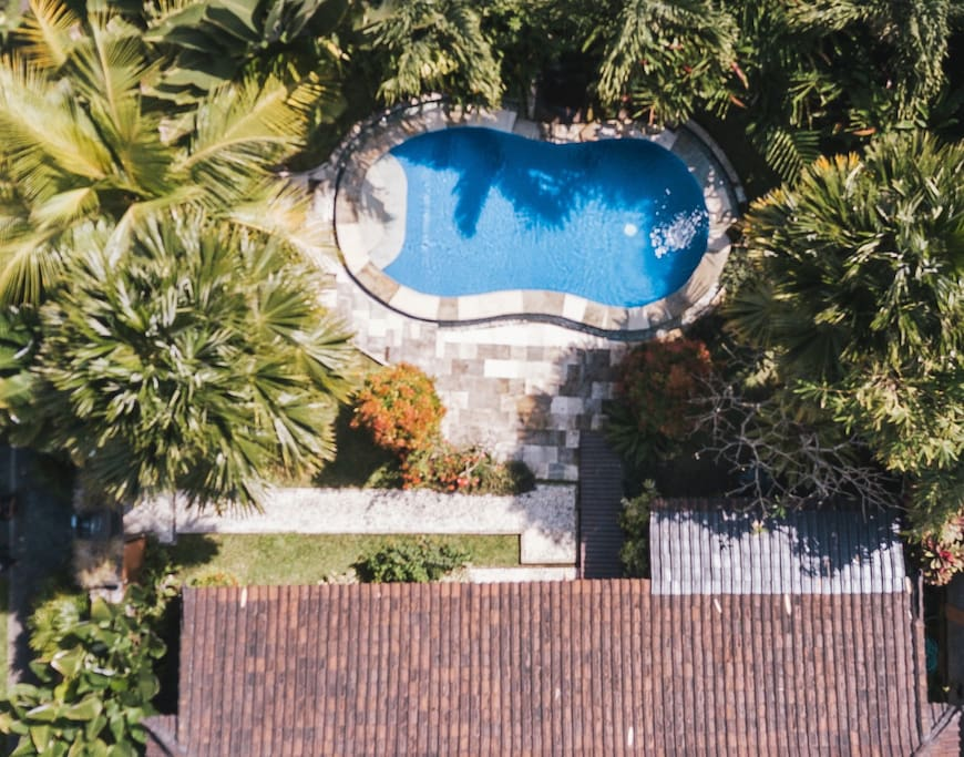 Seen from above, you see the lush garden surrounding the private pool. The pool, clad in deep blue tiles and encircled with tiles made of sand stone is filled with crystal clear water. It is approx. 7m x 2,5m.