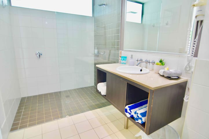 Your spacious bathroom with huge walk in shower and complimentary pool towels.