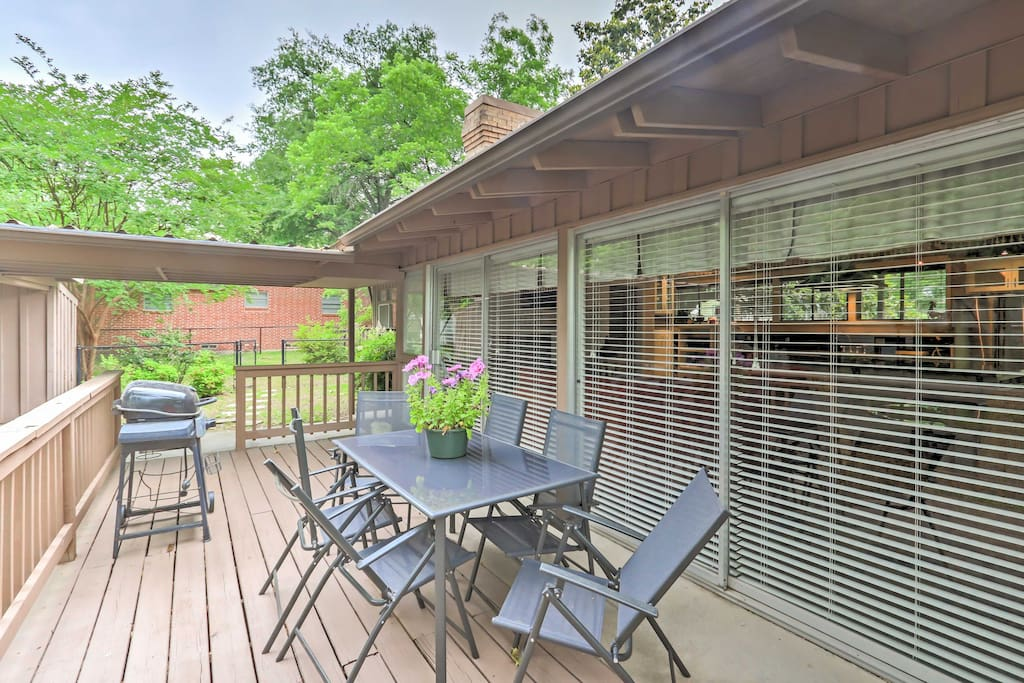 The spacious deck features seating, beautiful tree-lined views, and a gas grill.