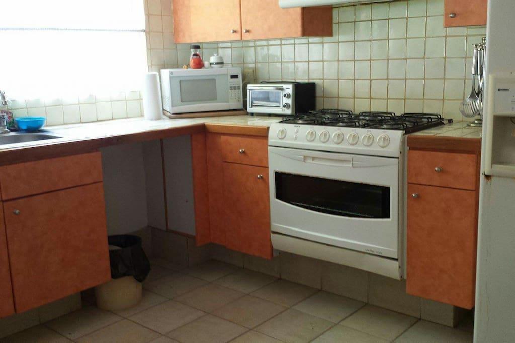 Cocina con refrigrigerador, estufa, horno, mini horno, lavabo, licuadora, microondas, utensilios, platos y cubiertos.