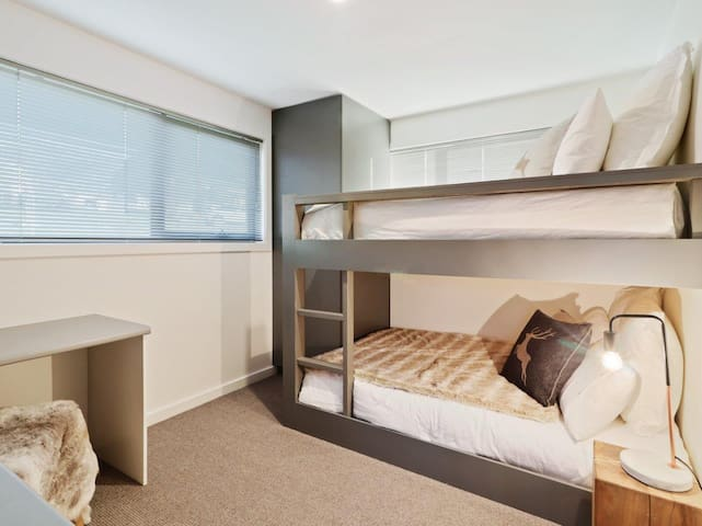 The downstairs bedroom offers custom super comfy double bed bunks, accommodating families and couples alike. There is also a fully fitted office space for those planning on staying connected to the office, or those studying.